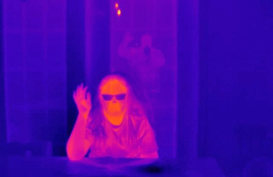 The young women seated has a glass door behind her and is waving at the thermographer, who can be seen in the reflection of the glass waving back.